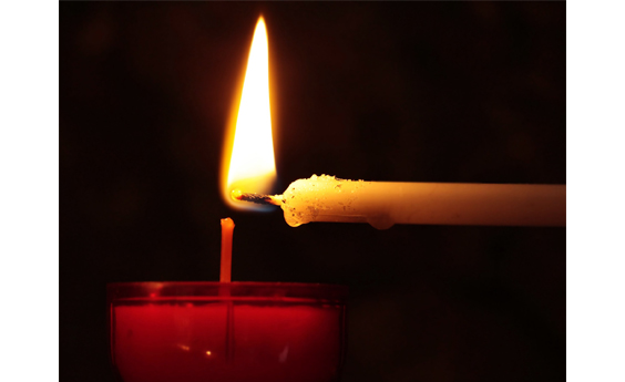 A red candle being lit from a thin white candle - dark background