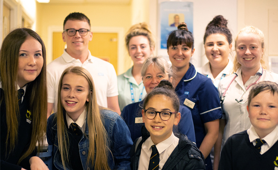4 school pupils standing with health care professionals behind them, in a care facility