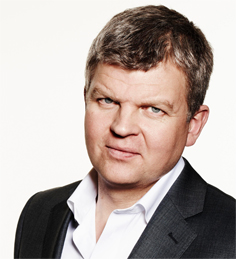 Head and shoulders of Adrian Chiles in black jacket and white open necked shirt
