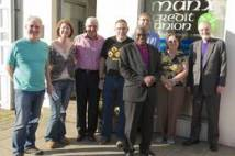 Archbishop with a group of people outside a shop on the Isle of Man