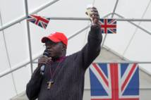 Archbishop raising a glass with Union flags behind