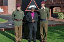 Archbishop standing alongside 2 soldiers on visit to Imphal Barracks