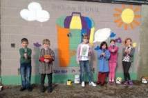 Children in front of playground mural with slogan 'Don't drop it, bin it'