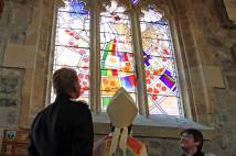 Archbishop looking at newly dedicated stained glass window in All Saints Pavement church