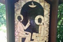 black and white picture on a board at Taize showing someone washing feet