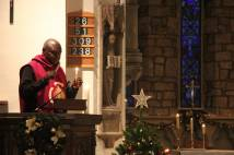 Archbishop holding candles by Christmas tree