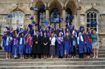 Graduates from Archbishop Sentamu Academy standing on steps of Bishopthorpe Palace throwing their mortar boards up in the air