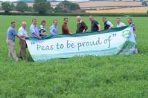 Farmers in a field holding a banner 'Peas to be proud of'