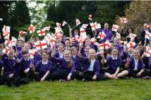 School pupils from Archbishop of York Junior school sitting on grass waving England flags