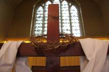 Crown of thorns hanging over a wooden cross in a church