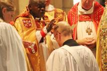Archbishop anointing a priest ordinand who is kneeling before him and other robed clergy