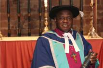 Archbishop of York standing in cap and gown in front of altar in Carlisle Cathedral with his honorary doctorate