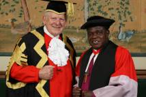 Archbishop and Chancellor of Durham University in red  black and gold academic robes