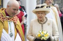 Archbishop Stephen Cottrell in gold and red robes standing next to HM The Queen who is dressed in matching hat and jacket carrying a posy of yellow flowers