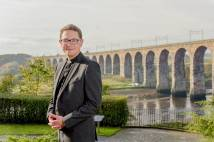 Clergyman standing outside in front of a viaduct