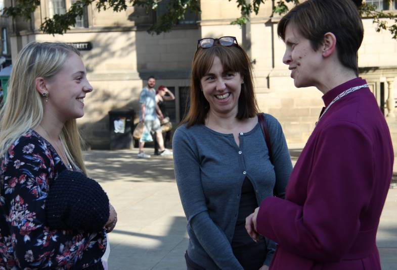 Bishop Libby speaks to two women on the street
