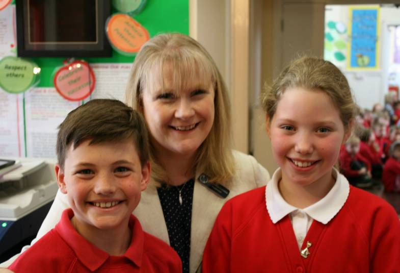 Teacher and 2 pupils smiling