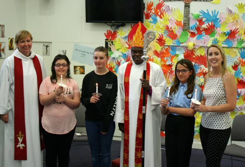 Archbishop standing with Chaplain and 4 students holding candles, from Archbishop Sentamu Academy following a baptism service