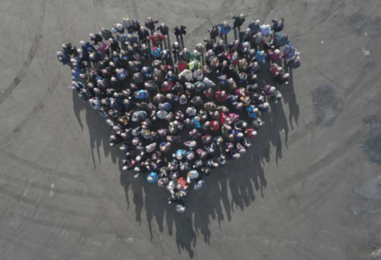 Aerial view of people standing together to create a heart shape