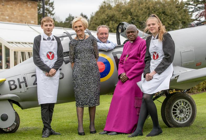 Archbishop with two students and Mary Berry and Jonathan Turner standing in front of a Spitfire aircraft