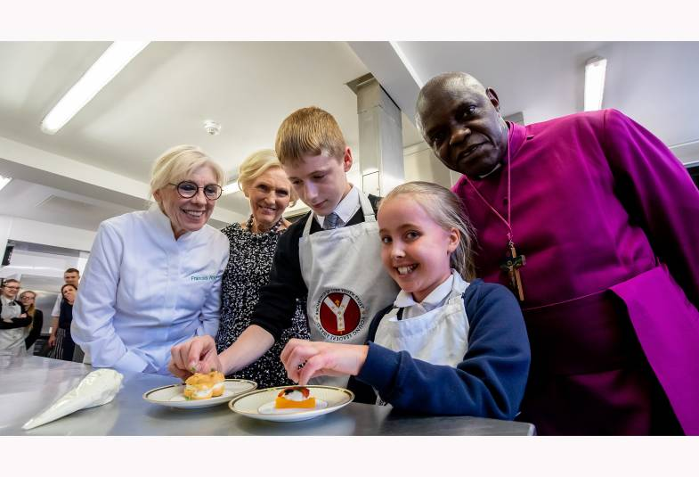 Frances Atkins, Mary Berry and the Archbishop standing behind two students with 2 plates of dessert in front of them.