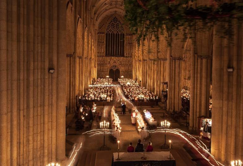 Inside York Minster showing procession of candlelight through the nave during a service