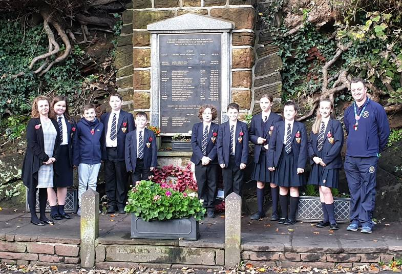 The pupils line-up at the war memorial, now updated with Gunner Southworth's name, alongside their teacher Heidi Jackson (left) and headteacher, Daniel Ballard (right)