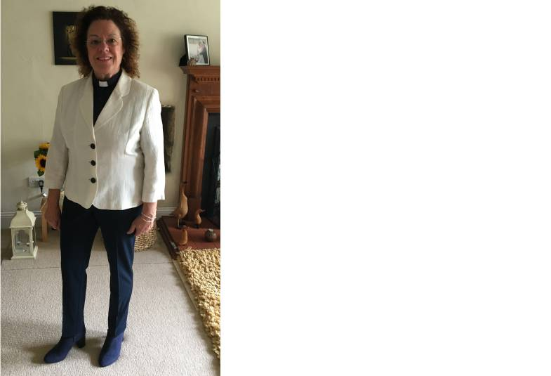 Female cleric standing in home living room dressed in black with white jacket