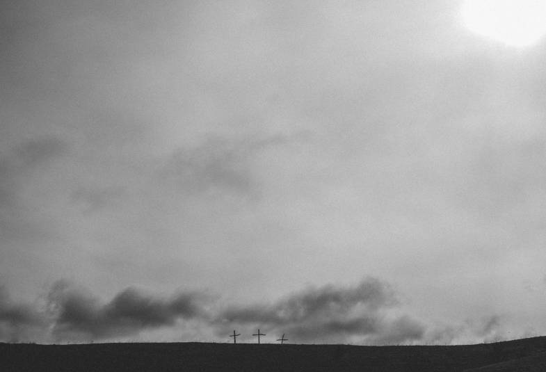 black and white photo of 3 crosses on the horizon