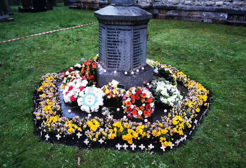 Flowers at the bottom of a memorial in a churchyard