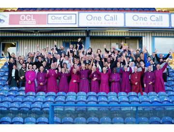 Bishops and their teams in the stands at Mansfield Football ground with arms raised in a shout
