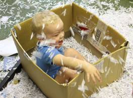 Toddler sat in cardboard box playing with shredded paper