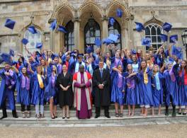 Graduating students from Archbishop Sentamu Academy on steps of Bishopthorpe Palace throwing their mitres in the air