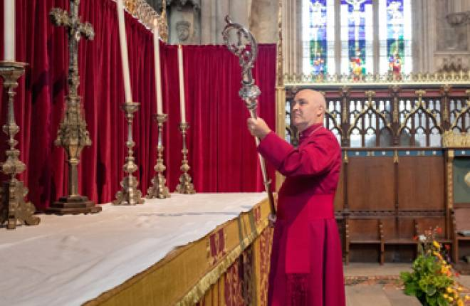 Archbishop holding silver crozier having just taken it off high altar in York Minster
